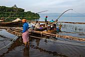Menschen entladen den Fang von Sambaza Fischen die von singenden Fischern auf dem Kivu See gefangen wurden, Cyangugu, Kamembe, Western Province, Ruanda, Afrika