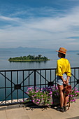 Young woman with sun hat and yellow blouse looks out from terrace of Emeraude Kivu Resort to island in Lake Kivu, Cyangugu, Kamembe, Western Province, Rwanda, Africa