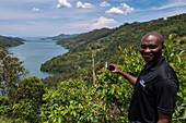 Man with smartphone stands above bay at Lake Kivu, near Gitesi, Western Province, Rwanda, Africa