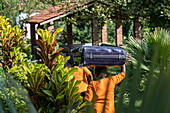 Hotel staff carries guest's suitcases on their heads at Rushel Lodge on the shores of Lake Kivu, Kinunu, Western Province, Rwanda, Africa