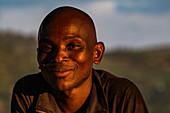 Portrait of a friendly Rwandan man in late afternoon light, Kinunu, Western Province, Rwanda, Africa