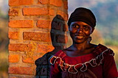 Portrait of a smiling Rwandan woman in late afternoon light, Kinunu, Western Province, Rwanda, Africa