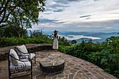 Junge Frau im Sommerkleid und mit Sonnenhut überblickt den Ruhondo See und die Berge von der Terrasse der Virunga Lodge, nahe Kinyababa, Northern Province, Ruanda, Afrika
