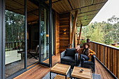 Young woman sits on the deck of the chalet in the luxury resort One