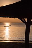 Silhouette von strohgedeckten Sonnenschirm und junger Frau die von Badeplattform ins Wasser vor dem Ong Lang Beach springt, Ong Lang, Insel Phu Quoc, Kien Giang, Vietnam, Asien