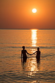 Silhouette of a romantic young couple holding hands in the water in front of Ong Lang Beach at sunset, Ong Lang, Phu Quoc Island, Kien Giang, Vietnam, Asia