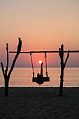Silhouette of young woman on swing at Ong Lang Beach at sunset pretending to be kicking the sun like football, Ong Lang, Phu Quoc Island, Kien Giang, Vietnam, Asia