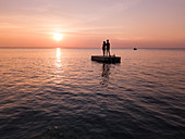 Aerial view silhouette of young couple standing on a bathing platform at sunset on Ong Lang Beach, Ong Lang, Phu Quoc Island, Kien Giang, Vietnam, Asia