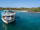 Aerial view of John's Tours No. 9 excursion boat and tourists snorkeling in clear water near beach with coconut palms, May Rut Island, near Phu Quoc Island, Kien Giang, Vietnam, Asia