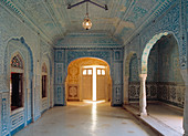 A striking blue room, detailed with lavish wall decorations, looking towards a door, opening into the outside and a blazing sunlight