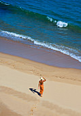 A woman dressed in a sarong with her back bare, walks in golden colored sand towards the water. Algarve, Portual.