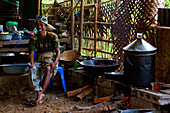 A Balinese cook, sitting in a ramshackle kitchen in a hut, smoking and laughing. Bali, Indonesia.