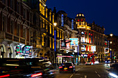 An eveing shot of traffic and neon lights in Shaftesbury Avenue in London, UK.