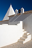 A white chapel building in Algarve Portugal. Architectural shot focusing on spahes, shadows and forms.