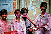 Indian boys celebrating Holi with stroing colors in the faces and on their clothes. Shot in Jaipur, India