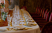 A table set with gold plates and gold gutlery and crystal glasses. Shot in Madrid, Spain.