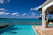 View of the ocean from an infinity pool and a bungalow beck.\nAntigua, West Indies