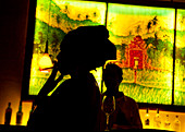 A black woman with headscarf smoking a cigarette , in silhouette against a lit junglescene sign at a bar.\nShot in Bali.