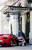 A guest arriving at a nice hotel, in a Ferrari, with a lot of posh shopping bags, being assited by the porter
