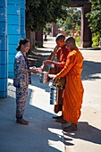 Woman offers food as alms to Buddhist monks, Oknha Tey Island, Mekong River, near Phnom Penh, Cambodia, Asia