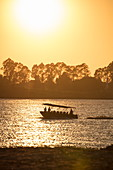 Silhouette of skiff dinghy from river cruise ship on the Mekong at sunset, near Preah Prosop, Mekong River, Kandal, Cambodia, Asia
