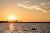 Silhouette of young couple during kayak excursion from river cruise ship on Mekong at sunset, near Preah Prosop, Mekong River, Kandal, Cambodia, Asia