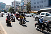 Zoomed image of people on mopeds and tuk-tuk on busy street, Phnom Penh, Cambodia, Asia