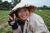 Portrait of a bold looking Vietnamese woman wearing a conical hat and working in a peanut field, My Luong Canal, Mekong River, near My An Hung, An Giang, Vietnam, Asia