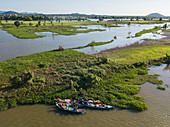 Aerial view of fishermen on a group of longtail boats along the banks of the Tonle Sap River with flooded rice fields behind, near Kampong Chhnang, Kampong Chhnang, Cambodia, Asia