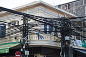 A chaotic yet functioning cluster of power and telephone lines in the city center, Phnom Penh, Cambodia, Asia