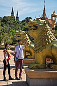 Young couple looking at dragon sculptures outside the Prasat Nokor Vimean Sour Temple, Oudong (Udong), Kampong Speu, Cambodia, Asia