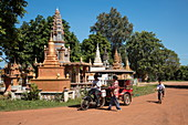 Moped rickshaw on dirt road in front of stupas, Kaoh Chen, Koh Chen Island, Kampong Cham, Cambodia, Asia