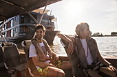 Young couple enjoys ride on skiff dinghy of river cruise ship on Tonle Sap River, Kampong Prasat, Kampong Chhnang, Cambodia, Asia