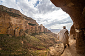 Rear view of priest walking on access trail to the rock-hewn Abuna Yemata Guh church, Gheralta Mountains, Tigray region, Ethiopia, Africa