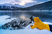 Photographer taking pictures of frozen Lej da Staz at dawn lying on the snow, Engadine, canton of Graubunden, Switzerland, Europe