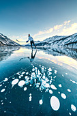 Ice hockey player skating on frozen Lake Sils covered of bubbles, Engadine, canton of Graubunden, Switzerland, Europe