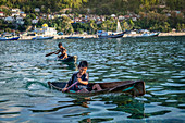 Local children in locally made dugout wooden canoes, Banda Besar, Maluku, Spice Islands, Indonesia, Southeast Asia, Asia