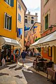 View of cafes and visitors on narrow street on a sunny day, Garda, Lake Garda, Province of Verona, Veneto, Italian Lakes, Italy, Europe
