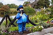 Figure in the garden, sailor, pipe, flowerbed, Greetsieler Sieltief, canal, Greetsiel, East Frisia, Lower Saxony, Germany
