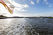 Ferry when leaving Bensersiel, harbor, fairway, flag, North Sea, sailing ship harbor, Bensersiel, East Frisia, Lower Saxony, Germany