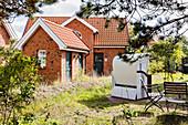 Typical island house with garden, beach chair, brick, grass, Spiekeroog, East Frisia, Lower Saxony, Germany