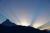 Sun rays behind the Machapuchare seen from Poon Hill, Nepal, Himalayas, Asia.