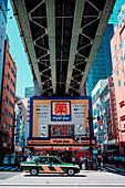 Taxi under a bridge in Akihabaras Hokuriku main street, Toyko, Japan