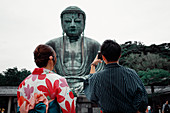 Koutokuin Temple with couple in foreground taking a photo of Buddha statue, Toyko, Japan