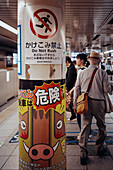 Pensioners on the subway with warning notices in the foreground, Toyko, Japan