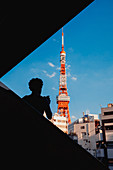 Siluette of a tourist photographing Tokyo Tower with his cell phone, Tokyo, Japan