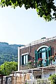 Balkon und Fensterläden eines Hauses auf einer Kulisse mit Bergen in Capri, Italien