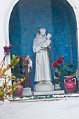 Religious statue and flowers in a wall niche in Capri, Italy