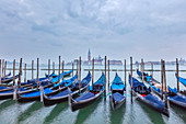 Resting gondolas on Riva degli Schiavoni with San Giorgio in the background in Venice, Veneto, Italy