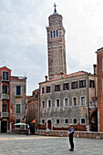Waiting gondolier on the Campo Sant'Angelo with the bell tower of Santo Stefano in Venice, Panorama, Veneto, Italy